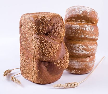 Two loaves of bread and wheat-ears on a white background. Stock Photo