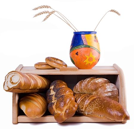 A bread-basket full of bread and a funny ceramic pot with wheat-ears. Isolated on a white background.