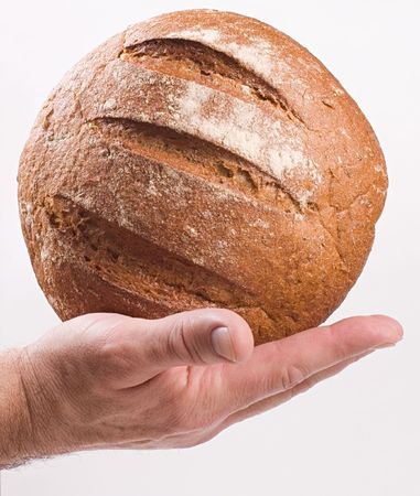 A mans hand holding a round loaf of brown bread.