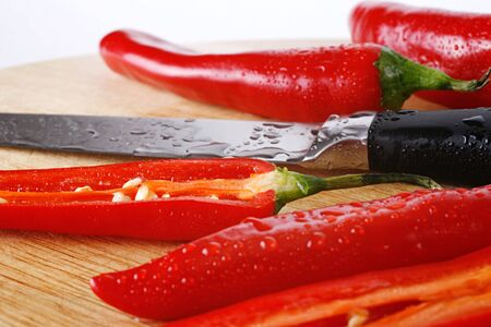 Red chili peppers and a knife, all covered with water-drops, on a preparation board. Close-up. White background. Stock Photo