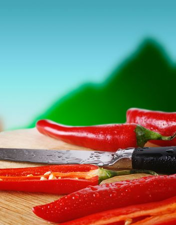 Red chili peppers and a knife, all covered with water-drops, on a preparation board. Close-up. Blurred background.