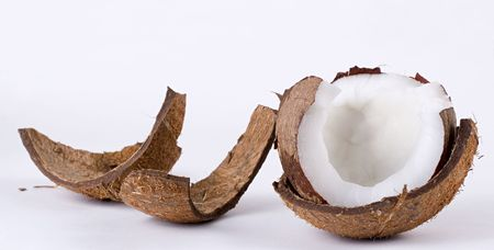 An open coconut and its broken husk on a white background.