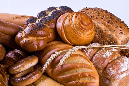 Variety of bread, bagels, buns and two wheat-ears.