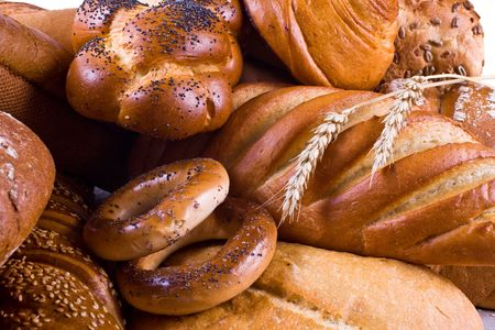 Variety of bread, bagels, buns and two wheat-ears. Close-up.
