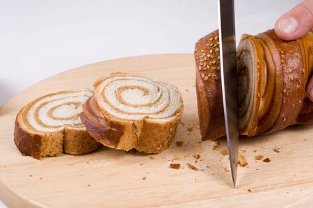A kitchen knife slicing a loaf of a long bread on a preparation board. Lots of crumbs on the board. Stock Photo