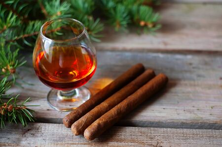 quality cigars and cognac on an old wooden table Stock Photo