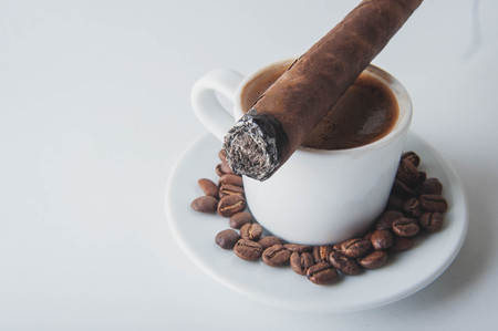Cup of coffee, coffee beans, ashtray with cigar on WHITE background.