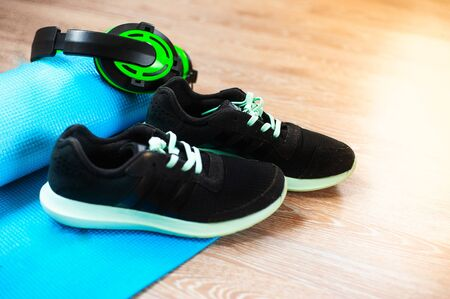 blue yoga and sports Mat, black sneakers with green laces, Stock Photo