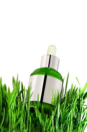natural essential oil in bottle with fresh green grass