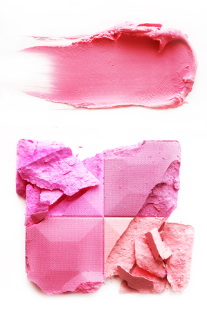 Eyeshadow pink and lipstick pink crushed and mixed isolated on a white background