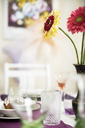 Empty glasses, cake and a bouquet of flowers on the table.