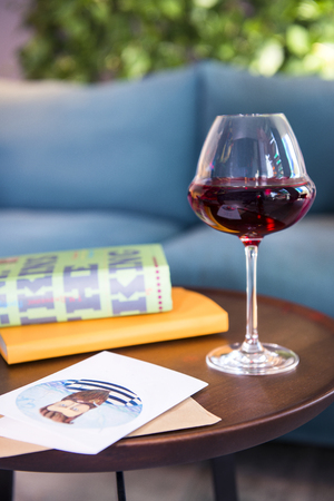 Book with wine glass and postcard on a wooden table Standard-Bild