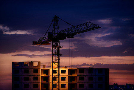 silhouette of crane and construction at sunset