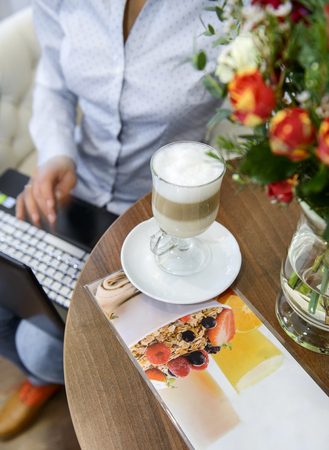 Cheerful attractive young woman drinking latte and using laptop in cafe