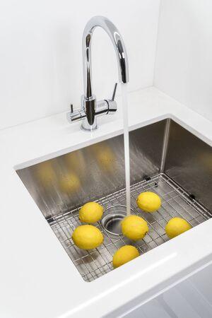 Washing lemons in the kitchen sink.