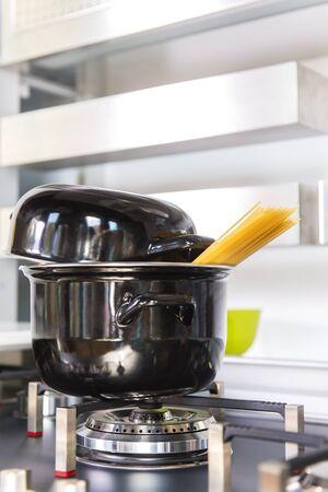 Spaghetti boiling in steel pan. Italian raw spaghetti.