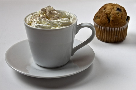 Creamy cup of coffe with fresh muffin. Focus on coffee. photo