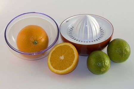 Two oranges,two limes and red plastic juicer