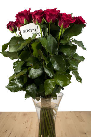 A bunch of roses in glass vase with note - sorry Stock Photo