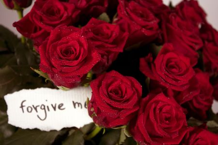 compliment: A bunch of roses in glass vase with note - forgive me