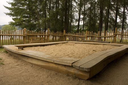 bounded: Sandpit at childrens playground, bounded by fence