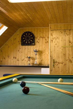 Billiards table with balls and cue sticks