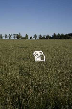 Plastic chair in field of grass