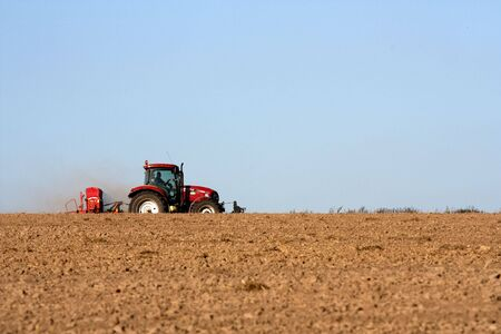 ploughing: Big tractor ploughing a field Stock Photo