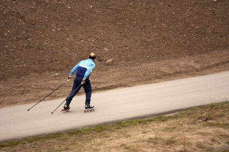 rollerskater: Lonely roller-skater with poles on a path