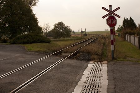 rail cross: Crossbarless rail and road crossing - stop sign and cross Stock Photo