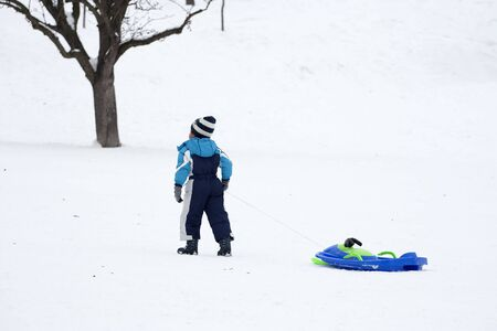 sledging people: Small colorful children pulling sledge in winter Stock Photo