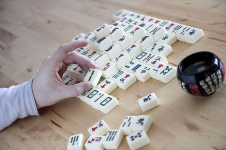 Mahjong player moving a game tile Stock Photo
