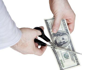 Cutting a hundred dollar bill in two parts Reklamní fotografie