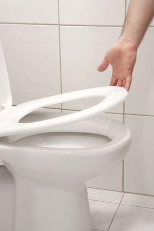 Man hand lifting up a toilet seat photo