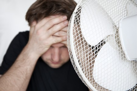 Sweat man in front of a ventilator Stock Photo