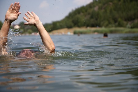 Drowning swimmer at a lake in summer