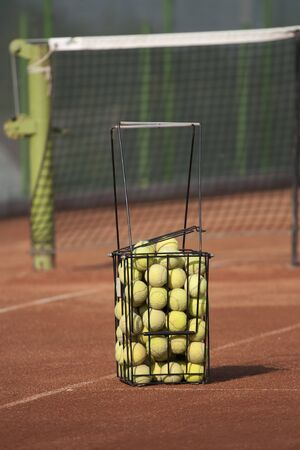 tennis clay: Basket with tennis balls on a court Stock Photo