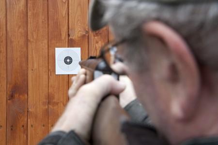 hombre disparando: Hombre de tiro con pistola de aire