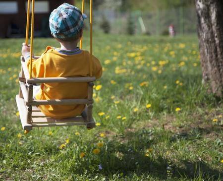 Boy swinging in a garden full of flowers Stock Photo