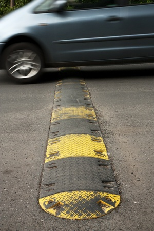 bumps: Speed bump on a road when a car is passing