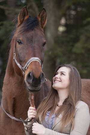 bbw: Young woman smiling and playing with a horse