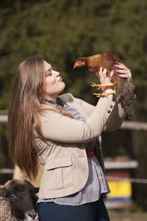 Young woman playing with chicken on a farm
