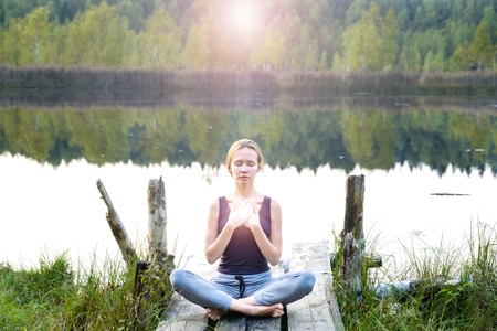 A beautiful woman sits in a pose of half lotus on a wooden pier on the shore of the lake, a stunning view of nature, she practices yoga meditation. The energy of Kundalini