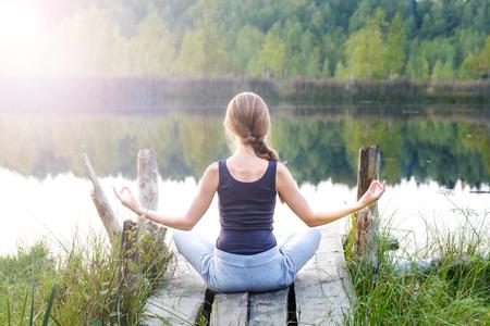 Eine schöne Frau sitzt in einer Pose aus halbem Lotus auf einem hölzernen Pier am Ufer des Sees, bietet einen atemberaubenden Blick auf die Natur und praktiziert Yoga-Meditation. Die Energie der Kundalini
