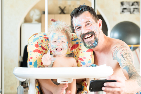 Father and little son laugh and do selfie on the phone. The faces and hair are stained with multicolored paints. Happy family. Great weekend together.