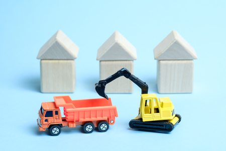 A yellow crawler excavator loads an orange dump truck against the background of houses built from wooden childrens cubes isolated on a white background. Construction equipment.