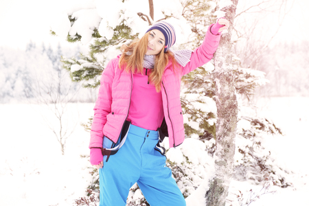Beautiful happy laughing red-haired young woman in a winter tracksuit covered in snow flakes. Winter forest landscape background.