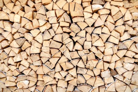 Background of chopped, sawn and stabbed stacked wooden logs.
