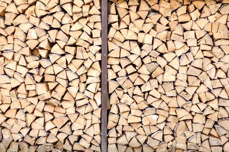 Background of chopped, sawn and stabbed stacked wooden logs