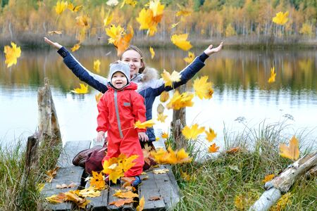 Mom and son sitting on the lake in the fall. Cute fun kids game and tossing leaves with mother. Mom and babys son spend time together. Yellow foliage. A happy family. Sunny good weather. Stock Photo